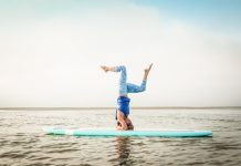 A woman practices yoga on a paddleboard