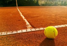 Close up of tennis ball on the clay court service line.