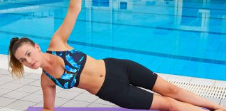 Female swimmer stretching poolside