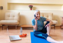 Senior woman using smartphone at home after exercise
