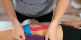 Hands of a female physiotherapist taping light blue medical tape over another pink tape on a patient's knee.